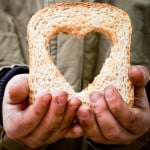 Helping the needy concept with dirty hands of a child holding slice of bread